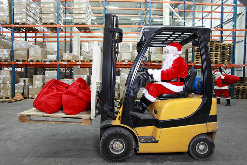 Santa picking Christmas lights in the warehouse